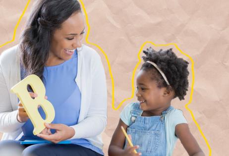 Em foto, é possível ver professora e criança lado a lado. A professora segura uma 'letra B' e a criança, que segura um lápis, observa a professora.