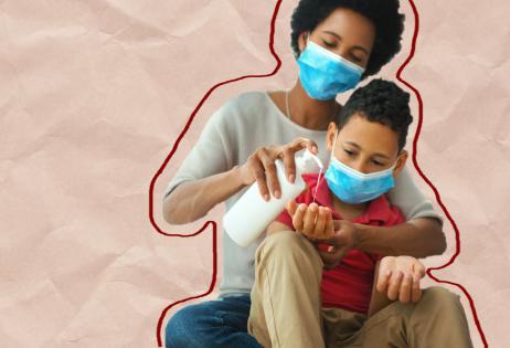 Mulher passa álcool gel na mão de menino no seu colo. Ambos usam máscaras de proteção.