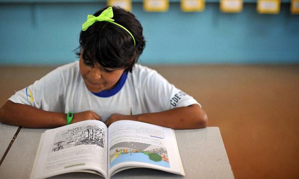 Estudante com livro didático. Foto: EBC