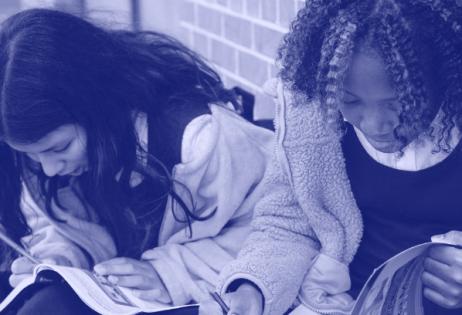 Em foto monocromática com filtro roxo aplicado, é possível ver duas meninas lendo