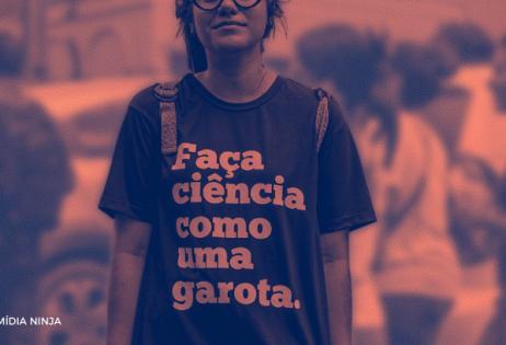 """Imagem alaranjada destacando garota com mochilas nas costas vestindo uma camisa com a seguinte frase """"faça ciência como uma garota"""". Há meninas circulando atrás da da garota com a camiseta.."""